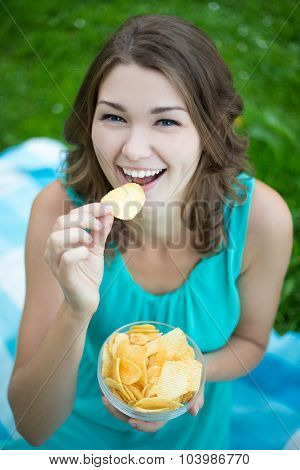 Cute Woman Eating Potato Chips In Park