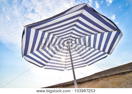 Blue And White Sun Beach Umbrella And Blue Sky With Clouds