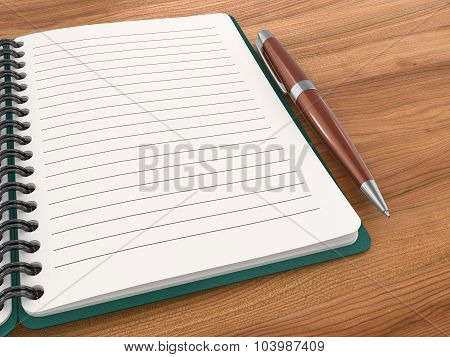 Notepad With A Ballpoint Pen On A Wooden Table.