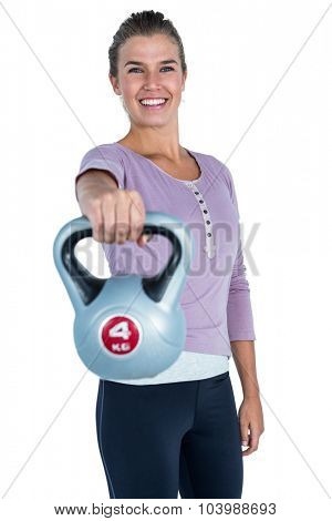 Portrait of cheerful woman exercising with kettlebell against white background