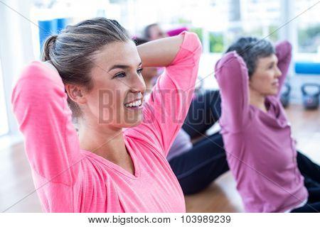 Fit women doing sit ups on hardwood floor in fitness studio