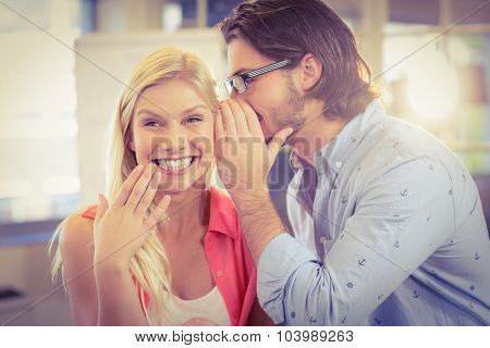 Happy businesswoman listening to male colleague in creative office