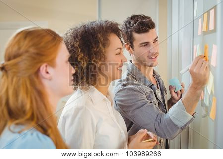 Businessman writing on glass wall as female colleagues looking at it during meeting in office