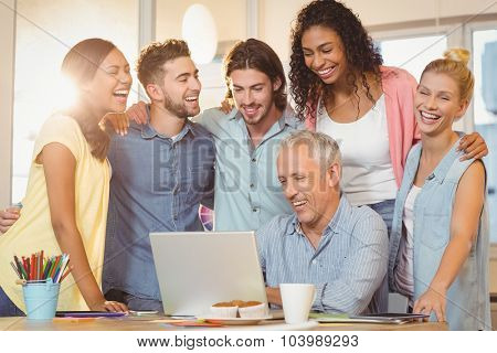 Happy business people looking at laptop in meeting room at creative office