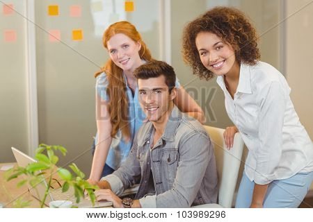 Portrait of smiling business people with laptop at work during office