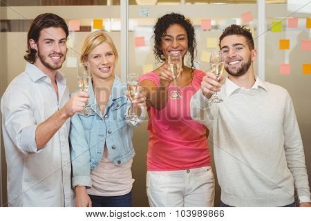 Portrait of happy colleagues holding champagne flute in party at creative office