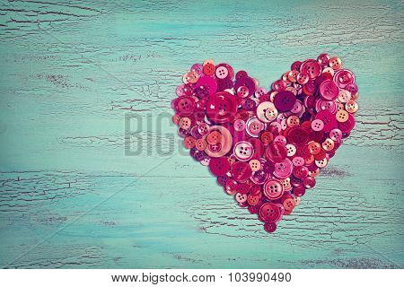 Heart from red buttons on a blue wooden background
