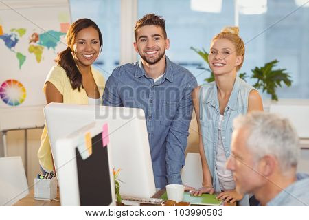Portrait of smiling business people using computer as male colleague working in creative office