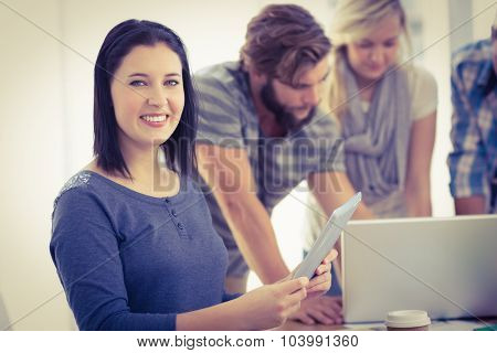 Portrait of smiling businesswoman with digital tablet at desk in creative office