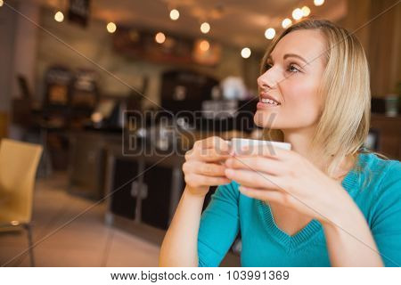 Young woman holding coffee cup looking away while sitting in cafe