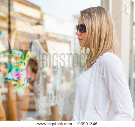 Woman Looking At Display Window In Fashion Store.