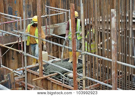 Construction Workers Using Concrete Vibrator to compact the concrete
