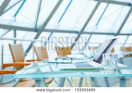 Laptop and glass of water on workplace in empty conference hall
