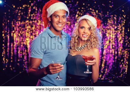 Santa guy and girl with cocktails looking at camera at party
