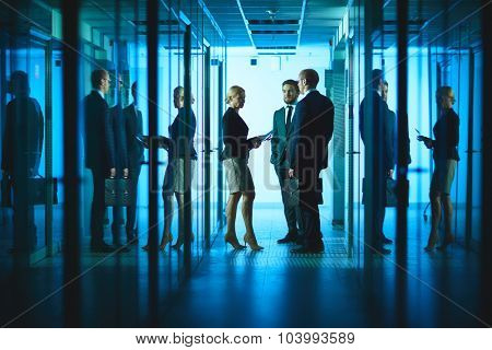 Group of colleagues consulting in corridor of business center