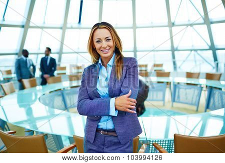 Pretty young businesswoman in suit looking at camera in conference hall