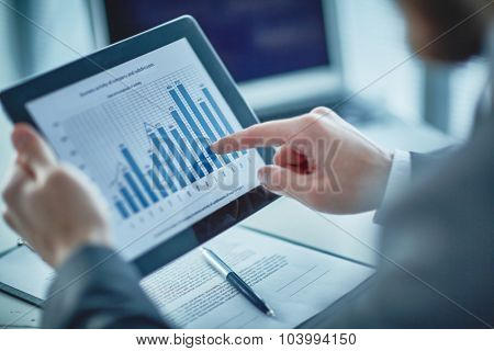 Businessman pointing at chart in touchpad
