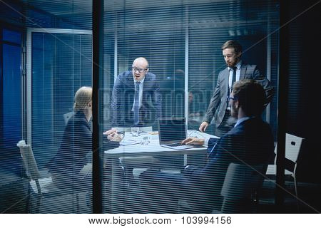 Group of co-workers discussing ideas at meeting in office