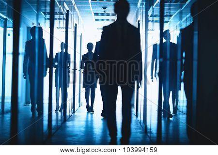 Elegant businesswoman and businessmen walking down corridor of business center