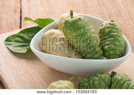 Noni Herbal Fruit On The Plate And Wood Floors.