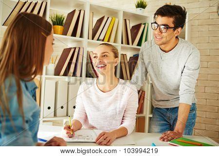 Happy college students talking during break between classes