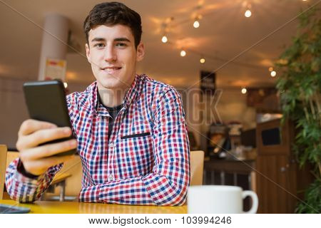 Portrait of happy young man using mobile phone at table in cafe