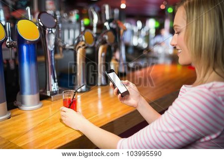 Young woman with mobile phone holding glass at bar counter