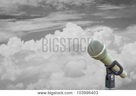 Microphone On A Stand Over Blurred Cloudy Black And White Sky