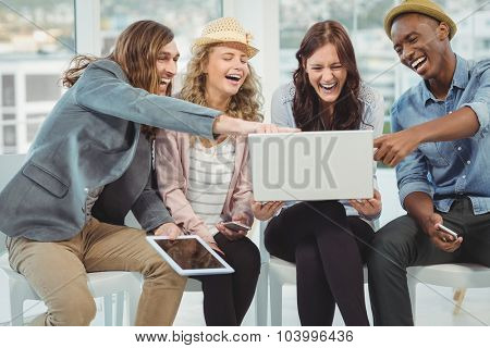 Business people laughing while pointing at laptop in office