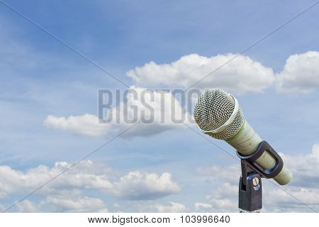 Microphone On A Stand Over Blurred Cloudy Blue Sky.