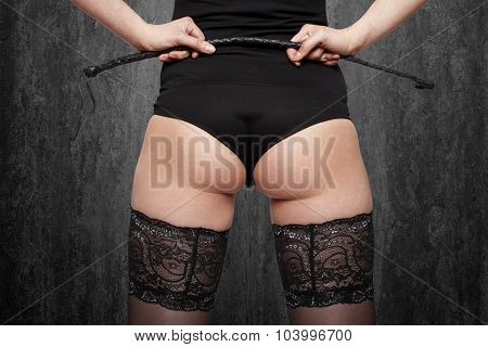 Sexy Brunette Woman In Stockings Holding Whip, Back View