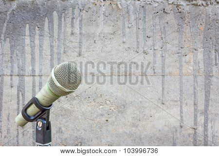 Microphone On A Stand With Blurred Concrete Wall With Cement Drips And Copyspace In The Middle.