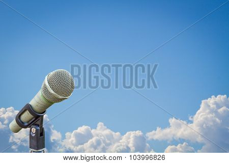 Microphone On A Stand Over Blurred Cloudy Blue Sky, With Wide Copyspace.