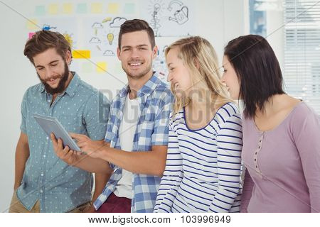 Portrait of happy man holding digital tablet standing with coworkers at office
