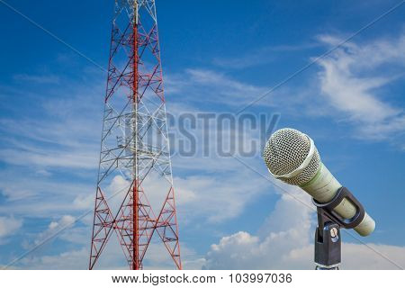 Microphone On A Stand With Blurred Telecommunication Tower And Cloudy  Sky