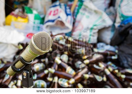 Microphone On A Stand With Blurred Beer Bottles And Plastic Sack