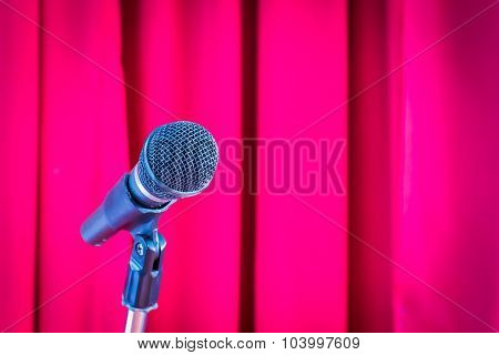 Microphone On A Stand With Blurred Red Curtain, Copyspace On The Right