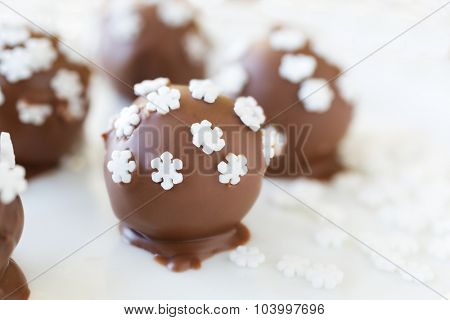 Homemade chocolate truffles decorated with candy snowflakes.