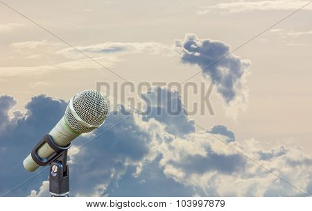 Microphone On A Stand With Blurred Gray Big Cloud In The Background Of Vanilla Sky.