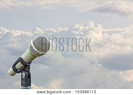 Microphone On A Stand With Blurred White Clouds Before Raining In The Evening, Copyspace On The Righ