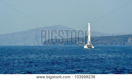 SANTORINI, GREECE - AUGUST 06, 2015: people on yacht near Santorini sea coast. Santorini is an island in the southern Aegean Sea, about 200 km southeast of Greece's mainland.