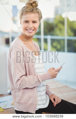 Portrait of smiling woman holding smartphone while sitting on desk in office