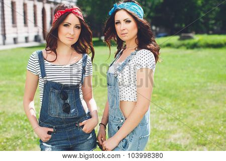 Portrait of two twins sisters stay together wearing bright bandanas and denim overalls best fiend enjoy amazing time together