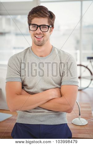 Hipster wearing eye glasses with arms crossed smiling while leaning at desk in office