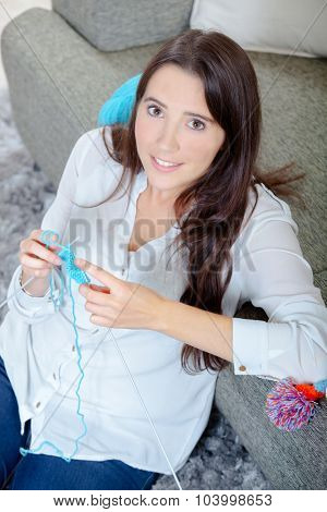 Young lady sat on floor knitting