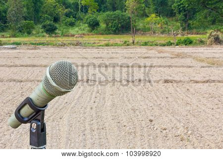 Microphone On A Stand With Blurredbackground Of Plowed Field With Tractor Traces, Copyspace.