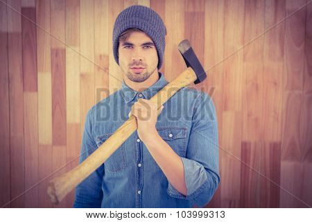 Portrait of confident hipster holding axe on shoulder while standing against wooden wall