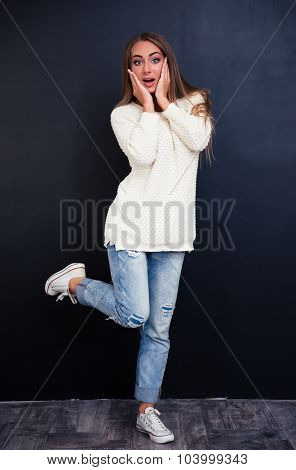 Portrait of amazed woman standing on gray background