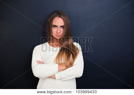 Portrait of angry woman standing with arms folded over gray background