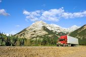foto of 18 wheeler  - a red truck goes through the canadian rockies
